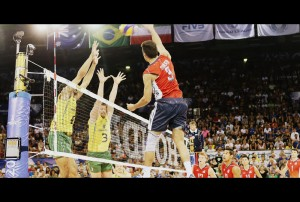 Taylor Sander (right) of USA spikes against De Souza and Carbonera (BRA)